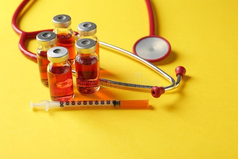 Ampoules avec le vaccin, la seringue et le stéthoscope photo libre de droits