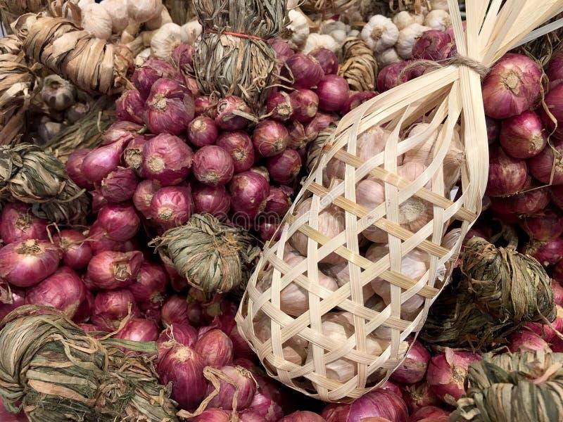 Ampoules d'ail, clous de girofle et échalotes rouges et blancs sur le fond en bois sur le marché local cru en bois de violette ro photos stock