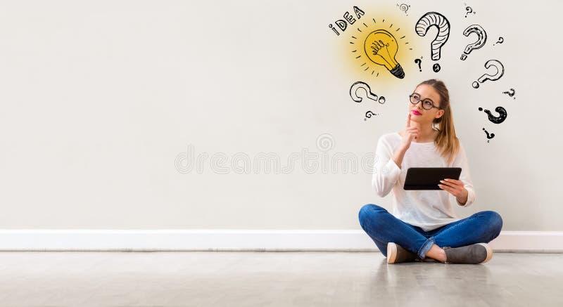 Ampoules d'idée avec des points d'interrogation avec la femme à l'aide d'un comprimé photos libres de droits