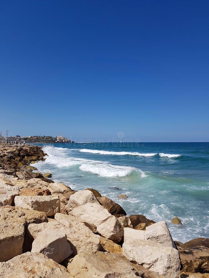 Ampuła kamienie na seashore fali rolce na brzeg linii i przerwie, fotografia stock