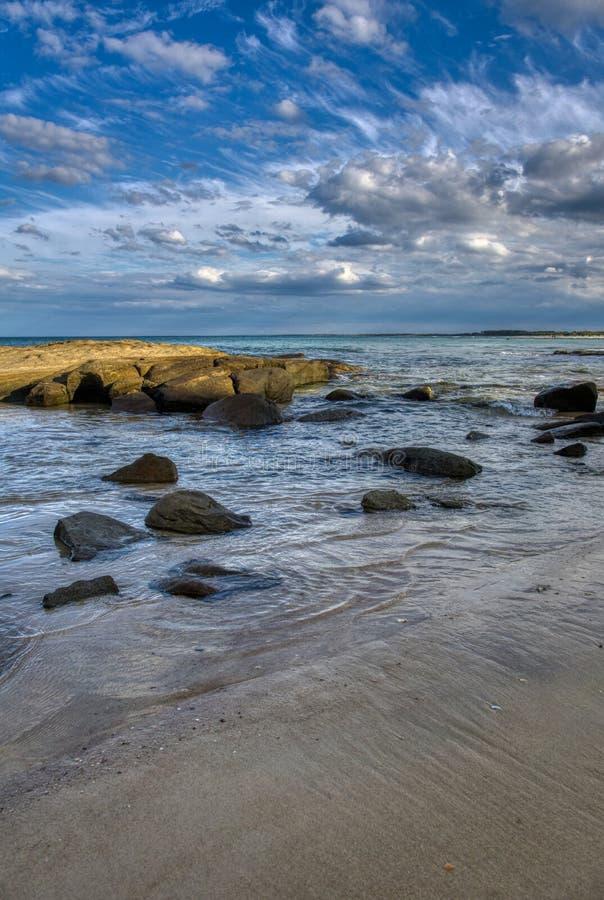 Ampuła kołysa i głazy w spokój płycizny wody morskiej spokoju machają niebieskie niebo z chmurami zdjęcia royalty free