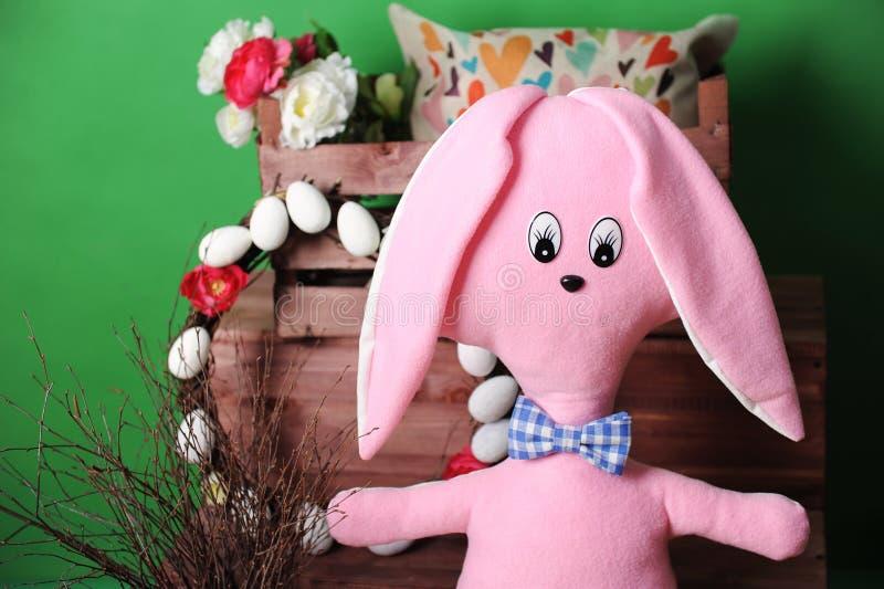 Ampuła różowi miękkiego królika w szkocka krata łęku krawacie z Wielkanocną dekoracją fotografia stock