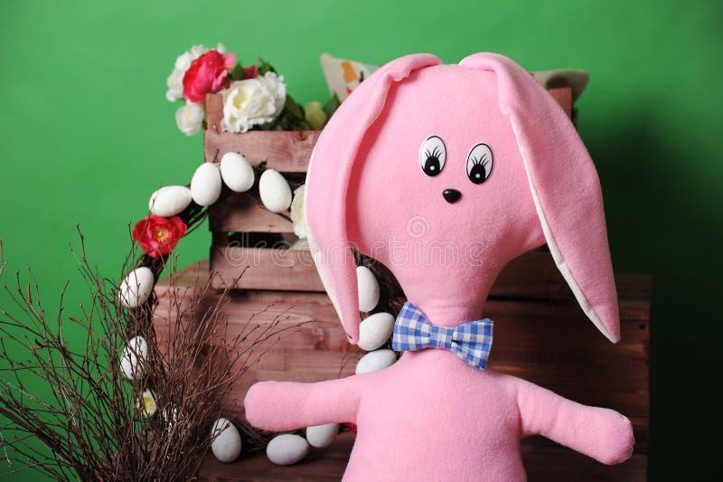 Ampuła różowi miękkiego królika w szkocka krata łęku krawacie z Wielkanocną dekoracją obraz stock