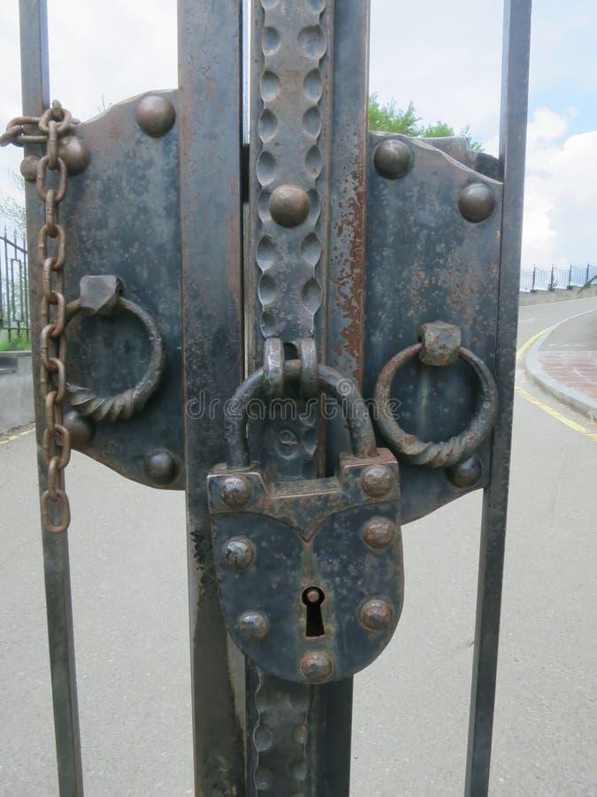 Ampuły żelaza kędziorek z łańcuchami przy wejściową bramą fotografia stock