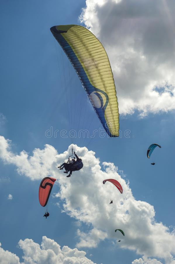 Ampuły grupa paragliders lata w niebieskim niebie przeciw chmurom obrazy stock