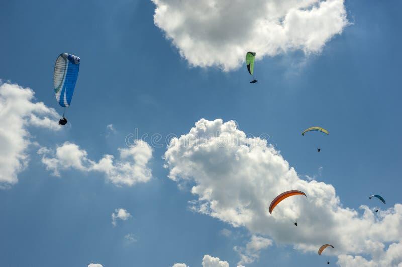 Ampuły grupa paragliders lata w niebieskim niebie przeciw chmurom zdjęcia stock