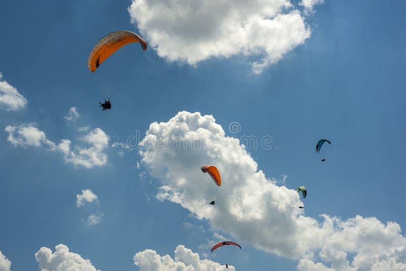 Ampuły grupa paragliders lata w niebieskim niebie przeciw chmurom fotografia stock