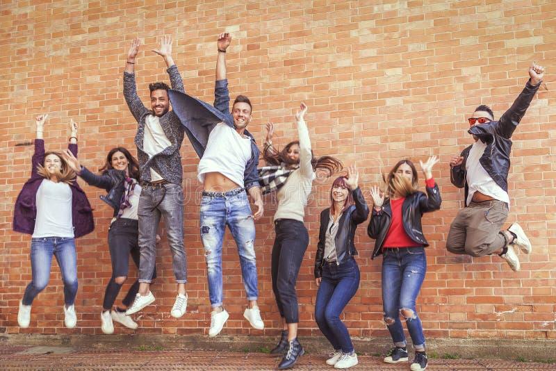 Ampuły grupa przyjaciele skacze wpólnie mieć zabawę zdjęcia stock