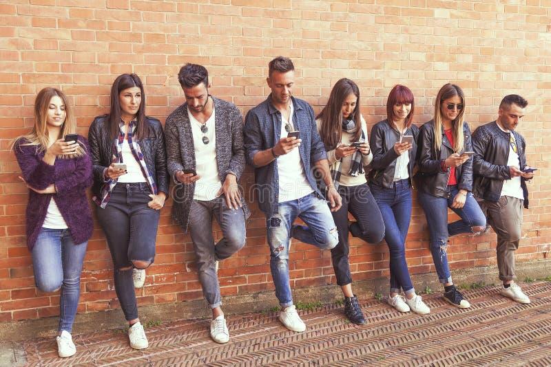 Ampuły grupa przyjaciele używa mądrze telefon przeciw czerwieni ścianie obrazy stock