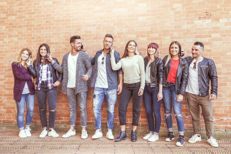 Ampuły grupa przyjaciele używa mądrze telefon przeciw czerwieni ścianie fotografia stock
