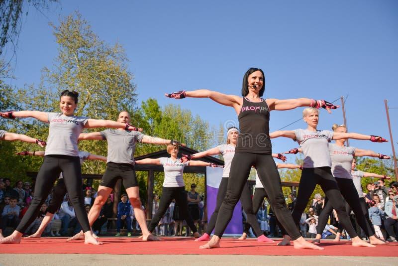 Ampuły grupa szczęśliwi młodzi ludzie z instruktora szkolenia Piloxing sportem na pogodnym wiosna dniu obraz stock