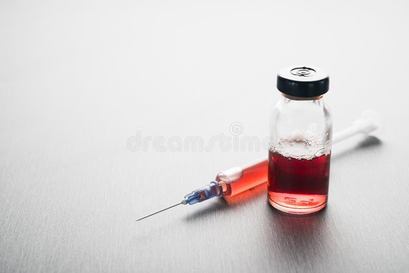 Ampule mit roter Medizin und Spritze stockfotografie