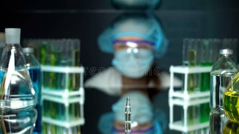 Ampule z przejrzystym cieczem na stole przed laboranckim pracownikiem, szczepionka obraz stock