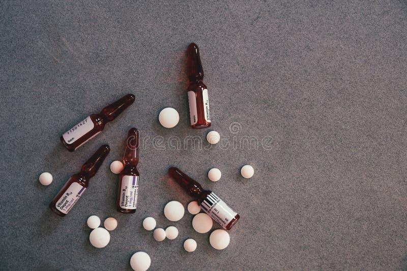 Ampules B12 и белые таблетки на конкретной таблице стоковые изображения rf