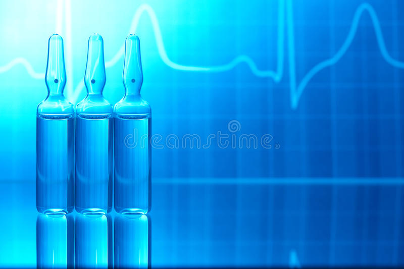 Ampules with EKG. Ampoules filled with medicine and EKG in background royalty free stock photo
