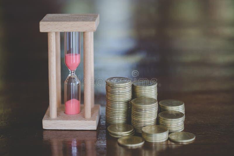 Ampulheta com as moedas no fundo de madeira, investimento do tempo e economia de aposentadoria Temporizador da contagem regressiv fotografia de stock royalty free