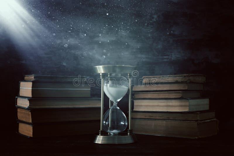 Ampulheta como o tempo que passa o conceito e livros velhos na frente do fundo preto da parede Foto conceptual na história, fant ilustração stock