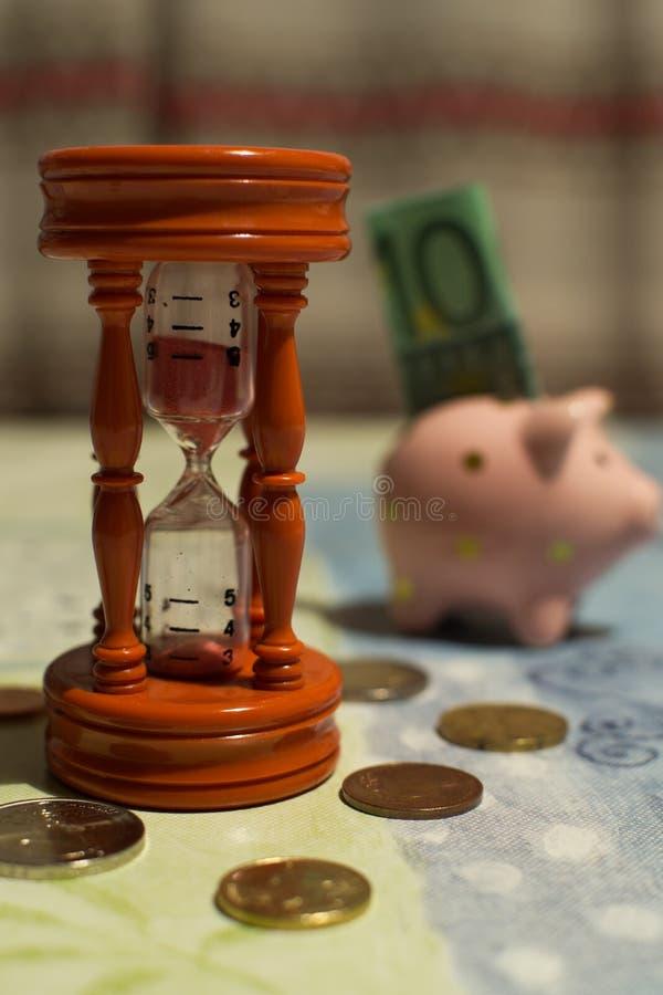 Ampulheta e mealheiro - Tempo é dinheiro imagens de stock royalty free