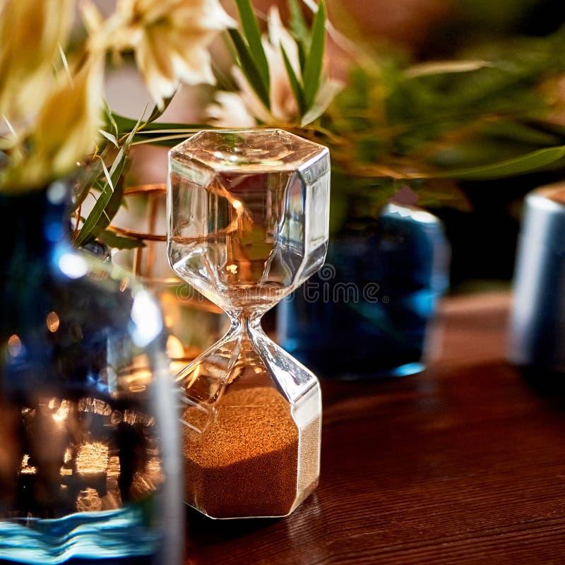 Ampulheta na tabela, com plantas verdes Conceito do tempo Aprecie o tempo imagens de stock