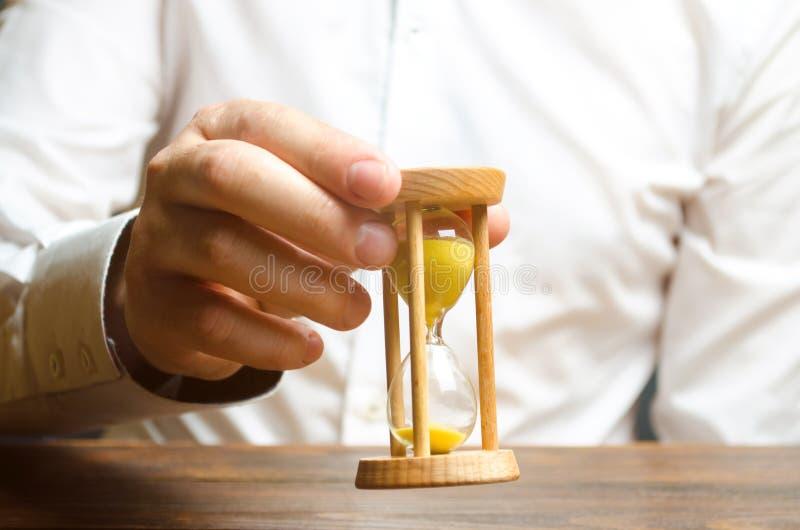 Ampulheta nas mãos de uma pessoa em uma camisa branca Gestão empresarial A eficiência do aumento da gestão de tempo, reduz custos fotografia de stock royalty free