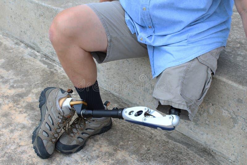 Amputé assis avec la jambe et la prothèse croisées image stock