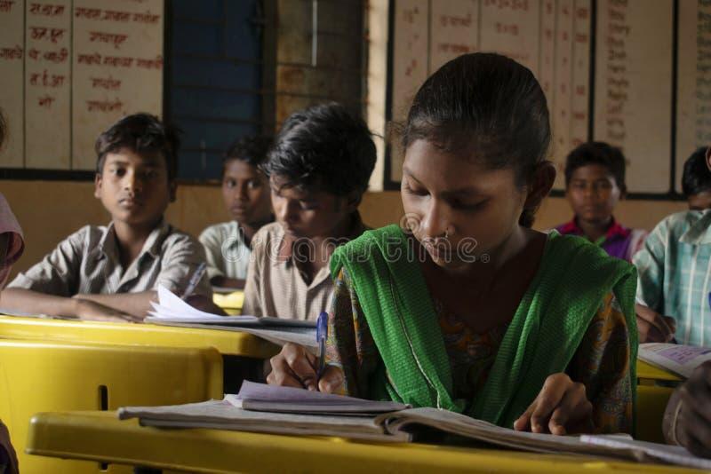 AMRAVATI, MAHARASHTRA die, INDIA, Augustus 2018, Meisje bij haar bureau bij lage school bij Ghuti-Dorp, Dharni Taluka schrijven stock fotografie