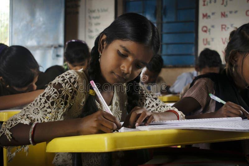 AMRAVATI, MAHARASHTRA, la INDIA, agosto de 2018, escritura de la muchacha en su escritorio en la escuela primaria en el pueblo de fotos de archivo libres de regalías