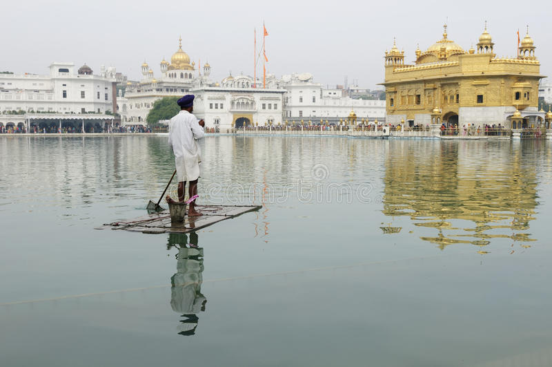 Amritsar, Golden Temple, India. INDIA, AMRITSAR - NOVEMBER 29: Sikh on the raft cleaning the saint lake on the area of temple complex in Golden temple (Sri stock images