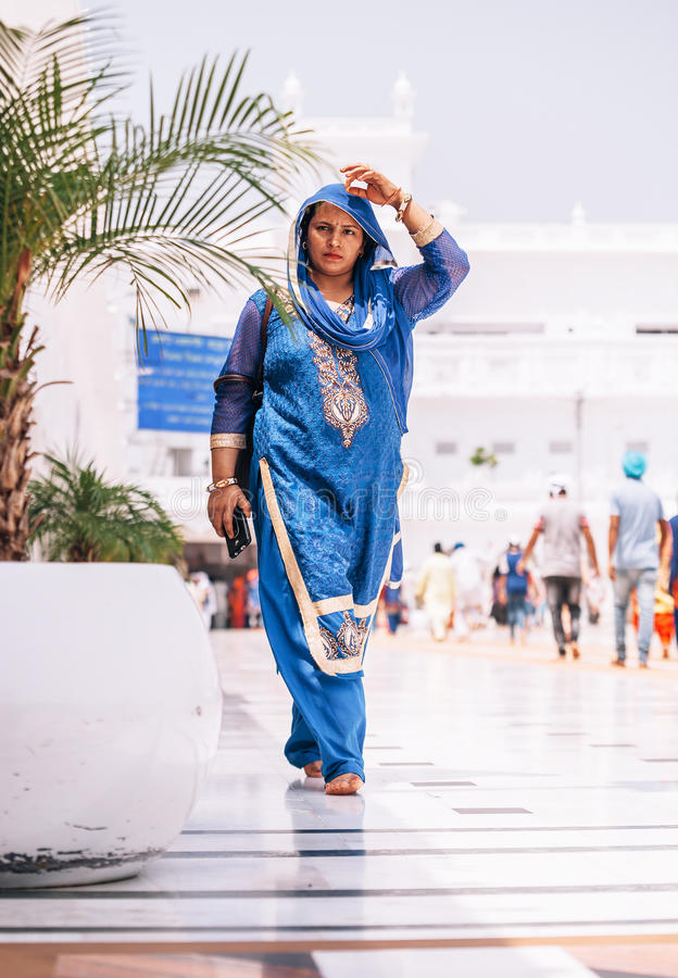 Amritsar, India - AUGUST 15: Portrait of indian woman dressed in female traditional sari saree garment walking by the Golden Tem. Ple Harmandir Sahib on August royalty free stock photography
