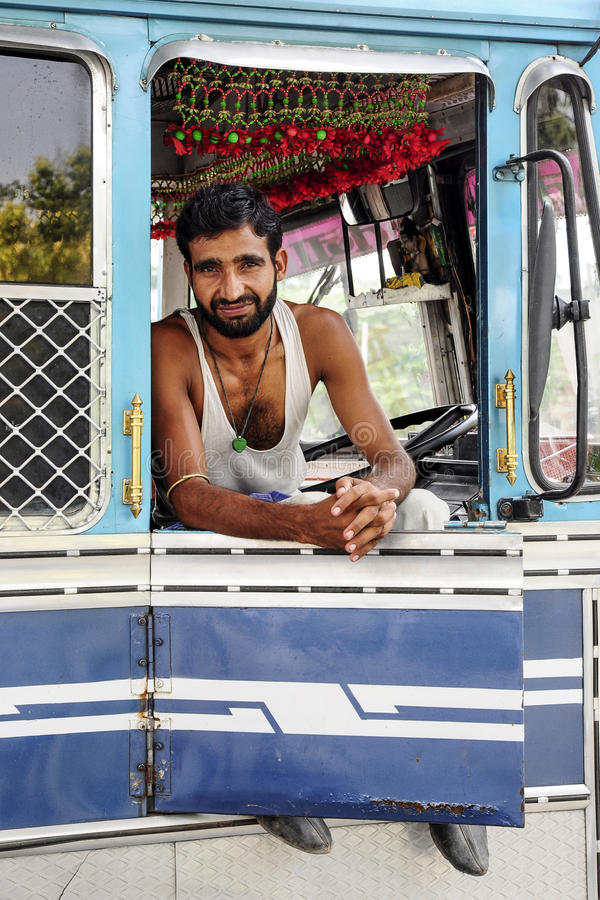 Amritsar, India, il 5 settembre 2010: Giovane uomo indiano, autista di camion, sedentesi e sorridente in suo camion L'India fotografia stock