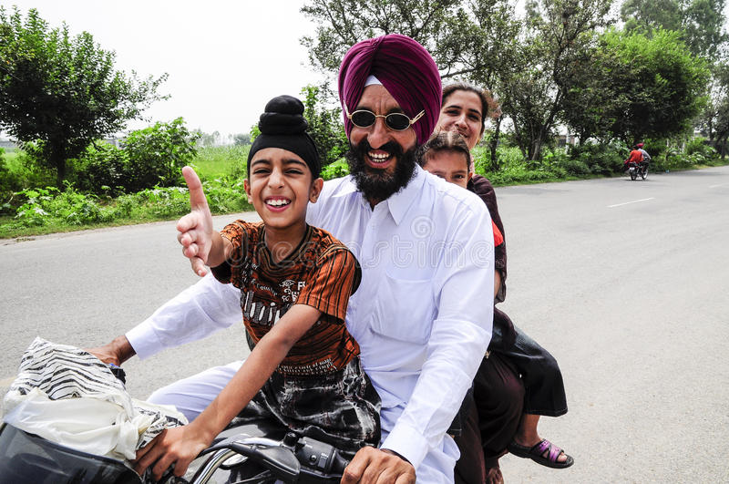 Amritsar, India, september 5, 2010: Sikh Indian family on a motorcycle with son pulling out his hand. royalty free stock photos