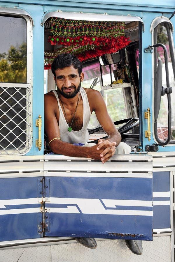 Amritsar, India, Wrzesień 5, 2010: Młody indyjski mężczyzna, kierowca ciężarówki, obsiadanie i ono uśmiecha się w jego ciężarówce zdjęcie stock