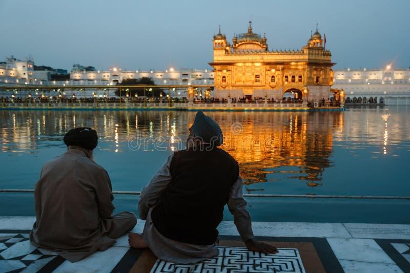 24 Amritsar Luty 2018, India Dwa indyjskiego sikhs obsługują siedzą blisko wody złota świątynia przy nocą zdjęcie royalty free