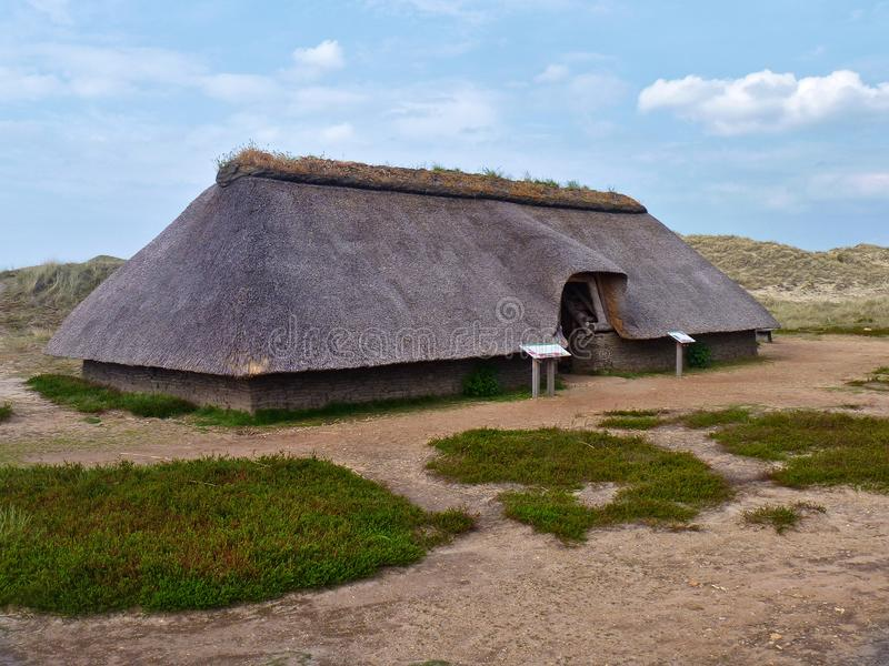 Amrum Tyskland - Maj 28th, 2016 - rekonstruktion av ett förhistoriskt för halmtäcka-tak för järnålder hus torva på ön av Amrum royaltyfri bild