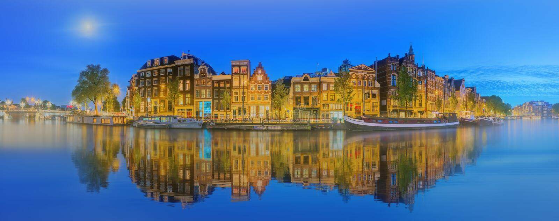 Amstelrivier, kanalen en nachtmening van de mooie stad van Amsterdam nederland stock fotografie