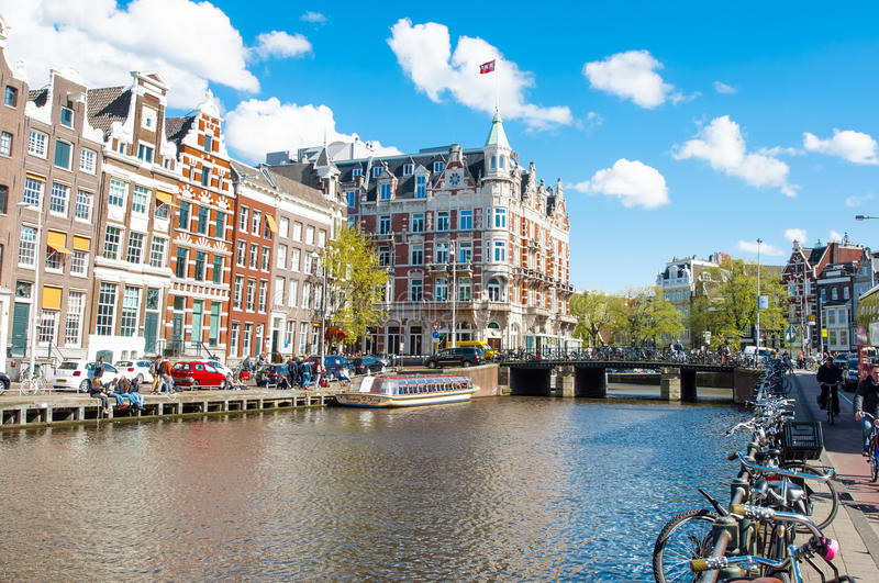 Amsterdão 30 de abril: O canal de Rokin com as bicicletas estacionadas ao longo do banco, hotel de l'Europe é visível no fundo fotos de stock