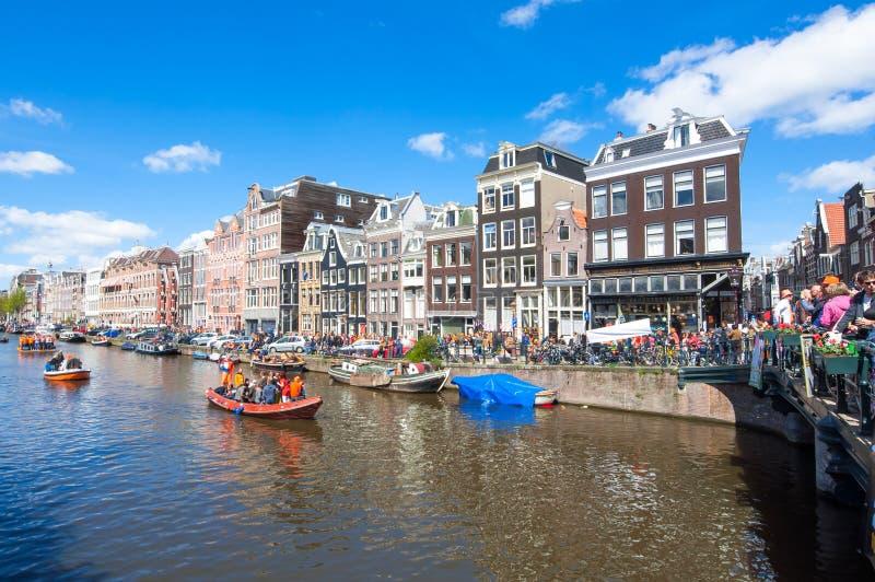 AMSTERDÃO 27 DE ABRIL: Os povos felizes comemoram o Dia em torno dos canais de Amsterdão, multidão do rei de povos apreciam o fes imagens de stock royalty free