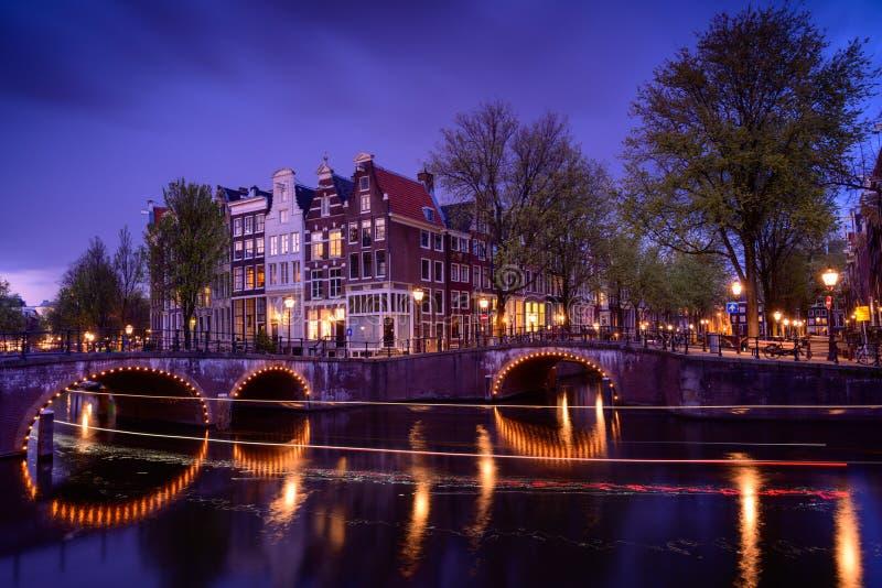 Amsterdão na noite com os barcos de flutuação no canal do rio, nivelando o tempo, viajando a Países Baixos imagens de stock