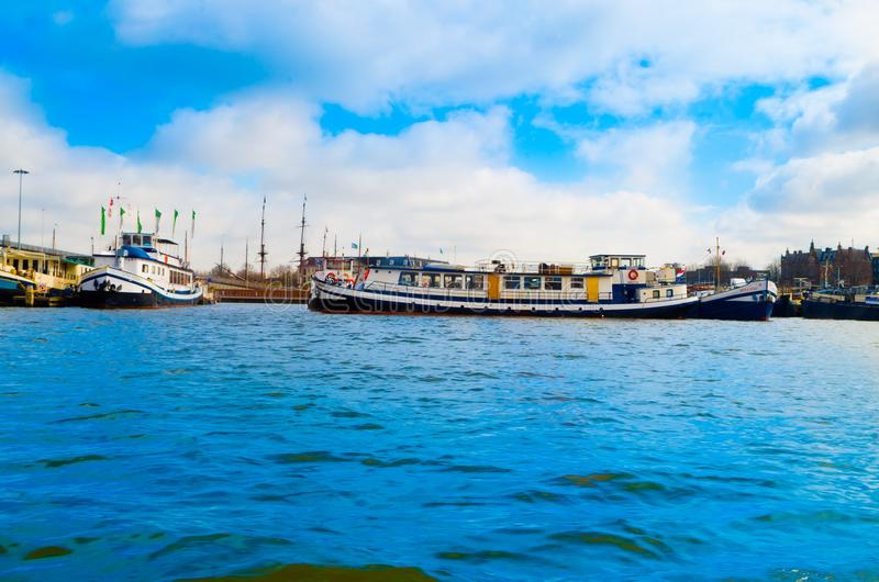 AMSTERDÃO, PAÍSES BAIXOS, ABRIL, 23 2018: Os barcos na costa dos canais, são o capital e a maioria de cidade populoso do imagens de stock royalty free