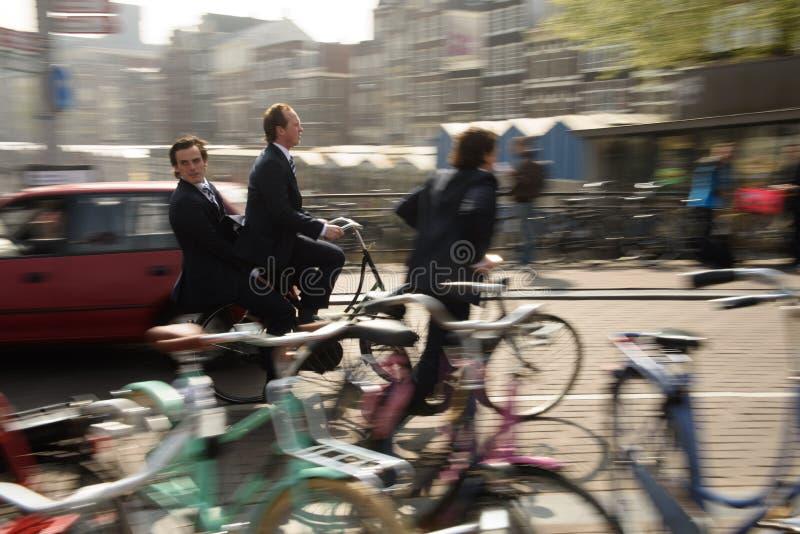 Amsterdão, Países Baixos, em abril de 2015: Montando uma bicicleta para trabalhar - Amsterdão imagem de stock
