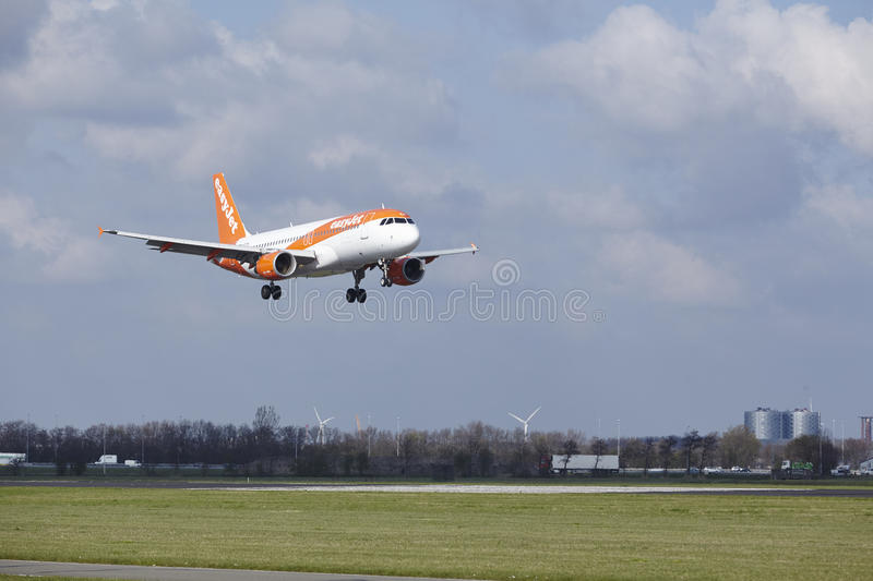 Amsterdam Airport Schiphol - Easyjet Airbus A320 lands. The Easyjet Airbus A320-214 with identification G-EZTH lands at Amsterdam Airport Schiphol The royalty free stock photos