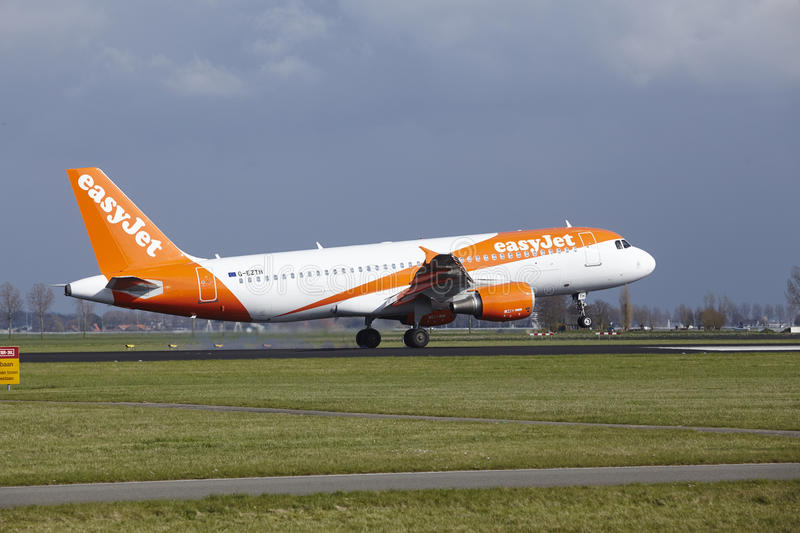 Amsterdam Airport Schiphol - Easyjet Airbus A320 lands. The Easyjet Airbus A320-214 with identification G-EZTH lands at Amsterdam Airport Schiphol The royalty free stock images