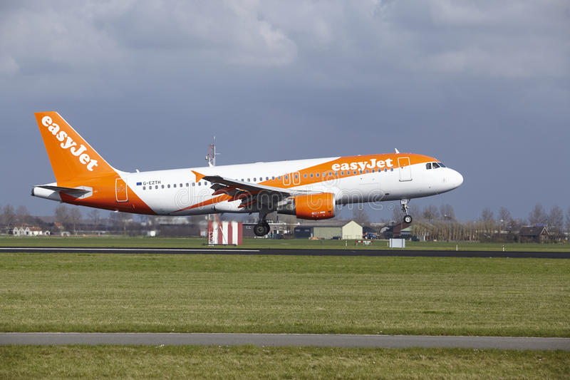 Amsterdam Airport Schiphol - Easyjet Airbus A320 lands. The Easyjet Airbus A320-214 with identification G-EZTH lands at Amsterdam Airport Schiphol The stock photo