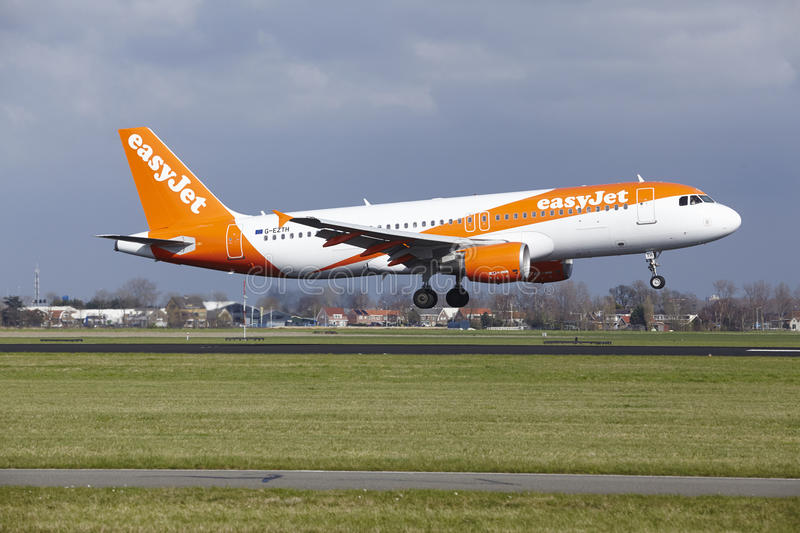 Amsterdam Airport Schiphol - Easyjet Airbus A320 lands. The Easyjet Airbus A320-214 with identification G-EZTH lands at Amsterdam Airport Schiphol The stock photography