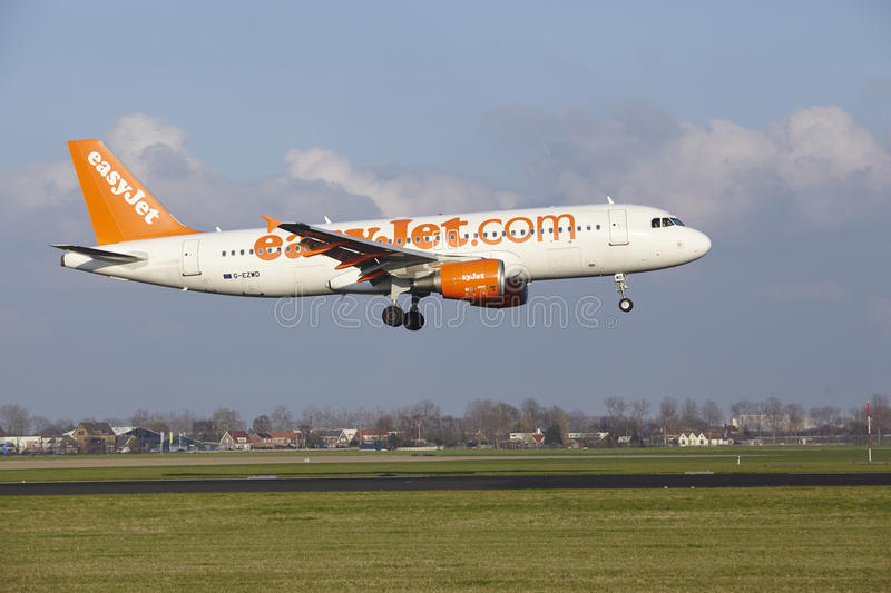 Amsterdam Airport Schiphol - Easyjet Airbus A320 lands. The Easyjet Airbus A320-214 with identification G-EZWD lands at Amsterdam Airport Schiphol The royalty free stock images