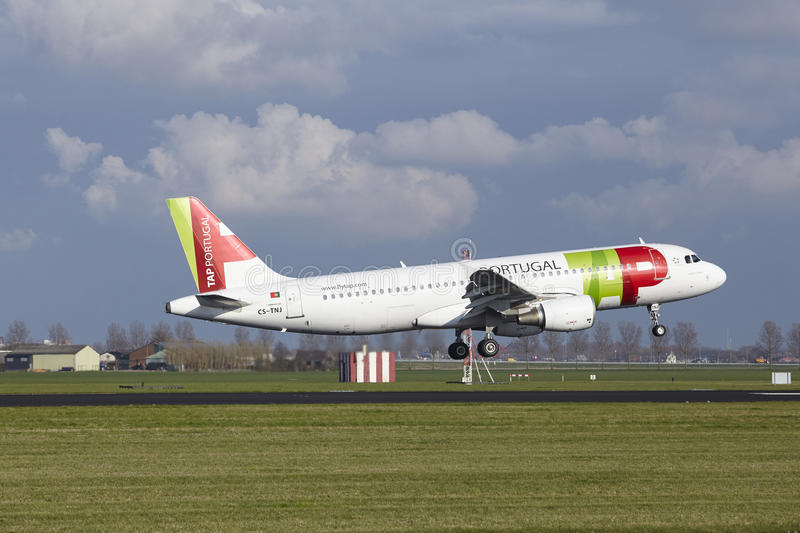 Amsterdam Airport Schiphol - TAP Portugal Airbus A320 lands. The TAP Portugal Airbus A320-214 with identification CS-TNJ lands at Amsterdam Airport Schiphol The royalty free stock image