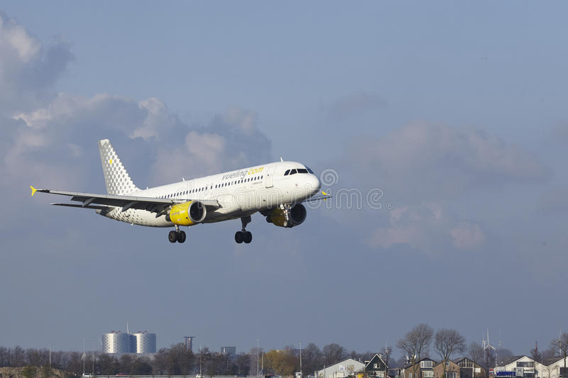 Amsterdam Airport Schiphol - Vueling Airbus A320 lands. The Vueling Airbus A320-214 with identification EC-KDH lands at Amsterdam Airport Schiphol The royalty free stock image