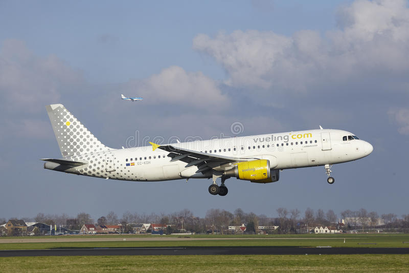 Amsterdam Airport Schiphol - Vueling Airbus A320 lands. The Vueling Airbus A320-214 with identification EC-KDH lands at Amsterdam Airport Schiphol The stock photography