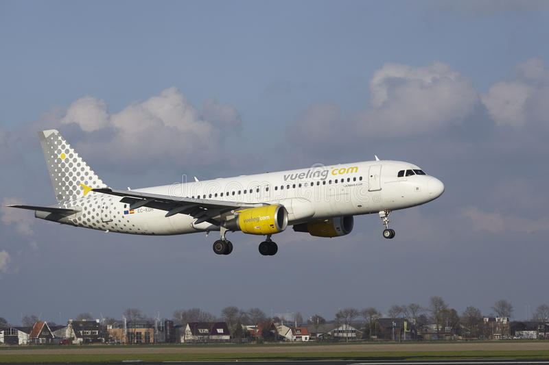 Amsterdam Airport Schiphol - Vueling Airbus A320 lands. The Vueling Airbus A320-214 with identification EC-KDH lands at Amsterdam Airport Schiphol The royalty free stock photo