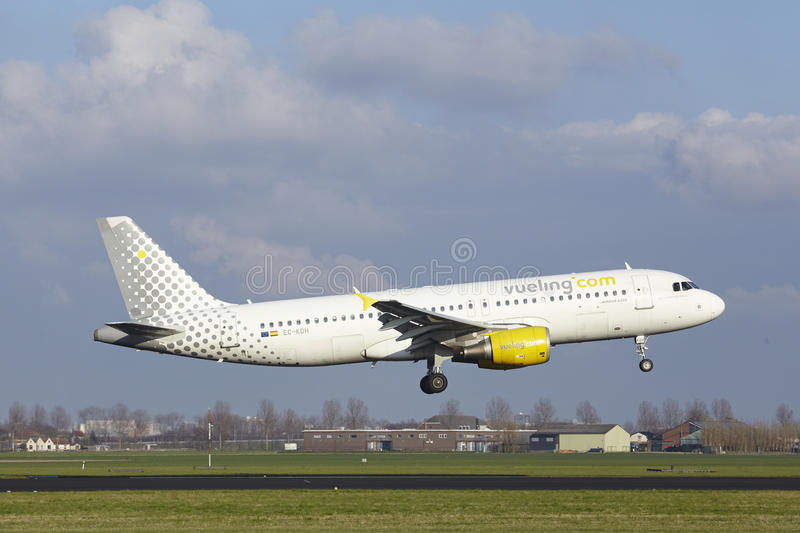Amsterdam Airport Schiphol - Vueling Airbus A320 lands. The Vueling Airbus A320-214 with identification EC-KDH lands at Amsterdam Airport Schiphol The royalty free stock images